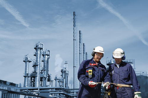 Two oil-workers, engineers, with refinery industry in background